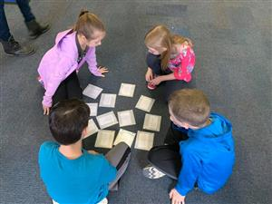 Four students in a group with game cards