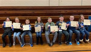 The eight contestants sitting in the gym.  The students are all holding certificates.