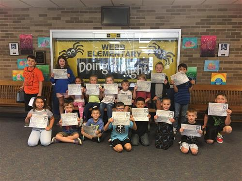 August students of the month standing in front of a yellow board with the words Webb Elementary Doing it Right