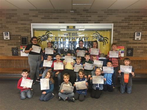 December students of the month holding certificates standing in front of yellow bulletin board with black letters which reads