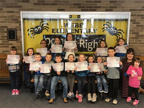 students of the month holding their certificates standing in front of a yellow bulletin board with the words Doing It Right