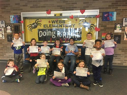 students holding certificates standing in front of yellow and black sign with the words Webb Elementary Doing It Right