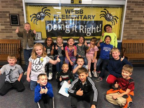 "Students sitting in front of a yellow and black sign that reads ""Webb Elementary Doning It Right"""