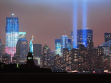 A picture of New York City skyline. One building is lit light the US flag. 2 lights where WTC was