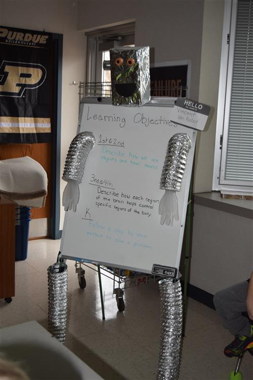 Robot with learning objective written on the whiteboard of his 'body'