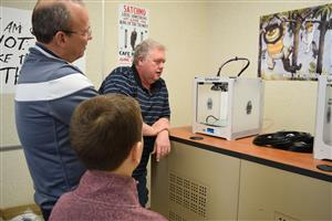 Mr. Rose, Dr. Clendening and Kail looking at 3D printer
