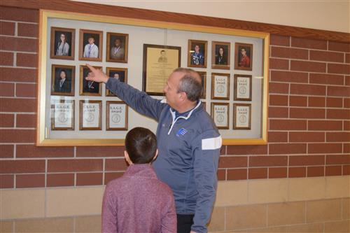 Dr. Clendening pointing to a picture of a student who had received a SAGE Award. Kail is looking at the pictures on the wall