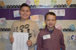 David and Kail standing next to each other smiling. David is holding a paper up to show.