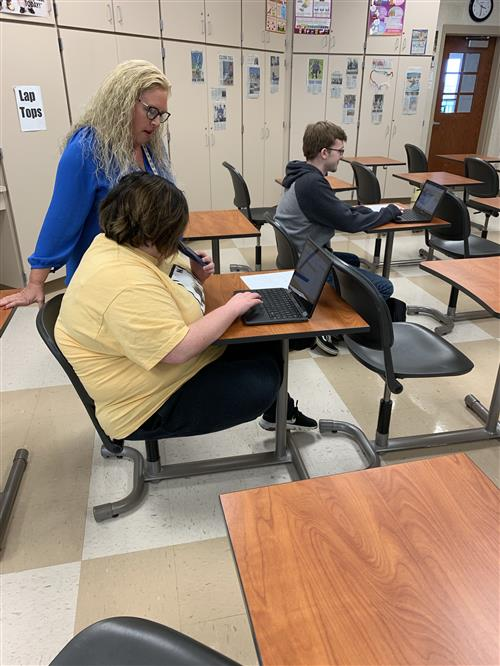 Mrs. Chadwell helping a student using a chromebook