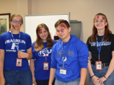 Four students standing together. Their faces have moulage and make-up on them.