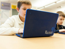 male student working on FCS issued Chromebook