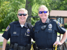 two female police officers in uniform smiling at camera