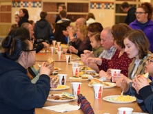 staff members and families eating at a long table.