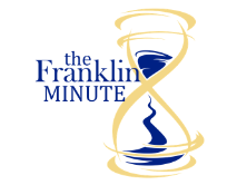 Yellow hourglass with blue sand swirling through it. In blue words, it says the Franklin Minute.