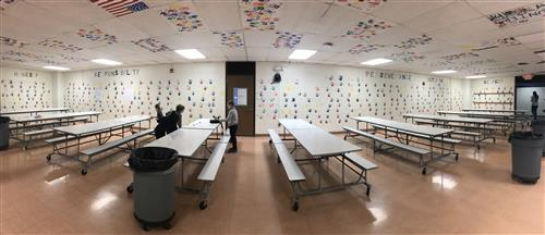 Photo of cafeteria where students are cleaning tables and there are handprints painted on the walls.